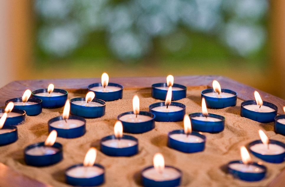 Small candle tea lights lit on a plinth with hazy green stained glass window behind