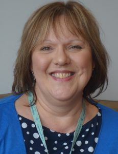 Wendy Duke, Family Support Worker. Wendy is wearing a blue cardigan and black and white spotted top. She is smiling.