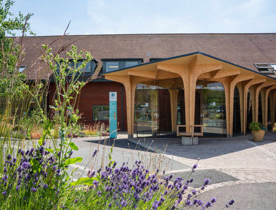 Wooden and glass entrance to hospice building, flower border to the left.