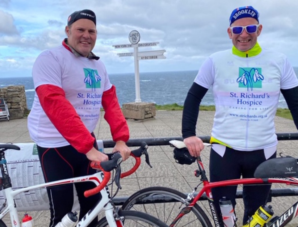Two people wearing St Richard's Hospice logo t-shirts standing next to their bicycles