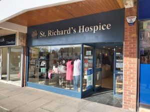 The shop front for the St Richard's Hospice shop in Bromsgrove. There are mannequins wearing clothes in the window and the door is open.