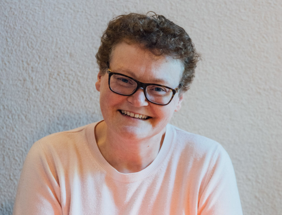 A smiling person with short hair, glasses, and wearing a light pink jumper.