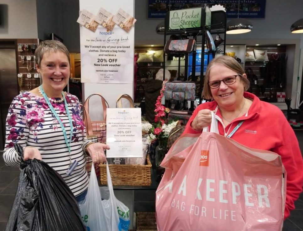 This button takes you to a page about where to donate goods to St Richard's shops. The image shows two smiling people standing together holding bags of donations.
