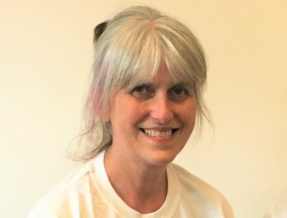 A person with light coloured hair smiles. They are wearing a white t-shirt.