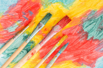 Five paint brushes with green, yellow and red