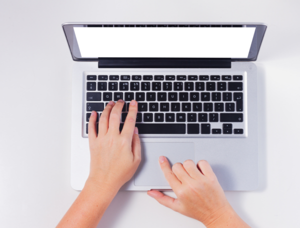 A pair of hands type on a laptop keyboard.