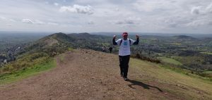 A man wearing walking gear and a white t-shirt bearing the St Richard's Hospice logo walks up a hill. He is on the Malvern Hills and there is a spectacular view of the ridge extending behind him. The sky is blue.