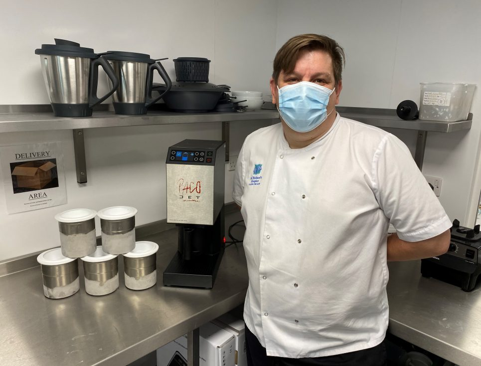 Head of Catering, Kevin Ratcliffe, stands in a chrome kitchen area next to an ice cream maker. He is wearing a white chef's top and blue face mask.