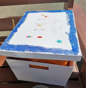A white box, outlined in bright blue glitter. This is a memory box used to help people cope with their bereavement.