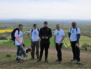 A group of people stand together wearing walking gear and white t-shirts with the St Richard's Hospice logo. They are on the Malvern Hills, with a great view of Worcestershire behind them. The sky is blue.