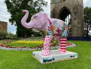 A pink, patterned elephant stands in a garden in front of a bed of flowers and St Andrew's Spire, Worcester, in the background.